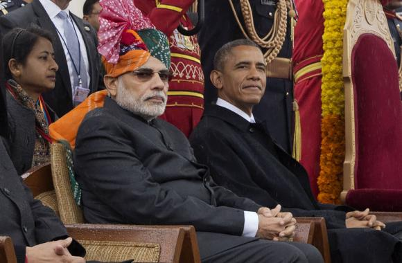 India's Prime Minister Modi and U.S. President Obama sit under umbrellas watching India's Republic Day parade in the rain together from their review stand in New Delhi