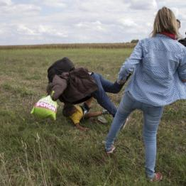 A migrant carrying a child falls after tripping on TV camerawoman (R) Petra Laszlo while trying to escape from a collection point in Roszke village, Hungary, September 8, 2015. REUTERS/Marko Djurica