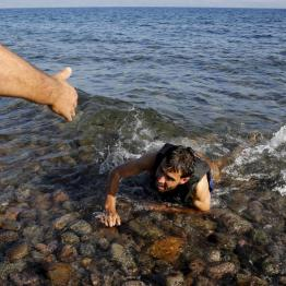 A local man helps a Syrian refugee who jumped off board from a dinghy as he swims exhausted at a beach on the Greek island of Lesbos September 17, 2015. REUTERS/Yannis Behrakis