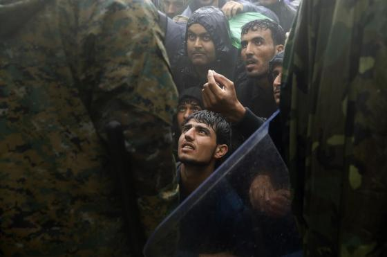 Migrants and refugees beg FYROM policemen to allow passage to cross the border from Greece into FYROM  during a rainstorm, near the Greek village of Idomeni, September 10, 2015. REUTERS/Yannis Behrakis