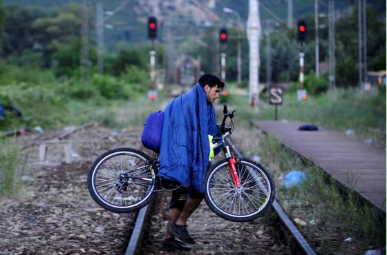 A migrant from Syria carries his bicycle on railway near the Greek border in FYROM  June 17, 2015. REUTERS/Ognen Teofilovski