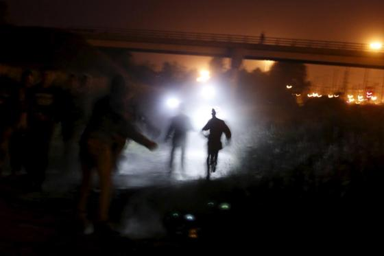 Migrants are illuminated by police torches as they run to cross a fence during an attempt to access the Channel Tunnel in Frethun, near Calais, France, August 5, 2015. REUTERS/Juan Medina
