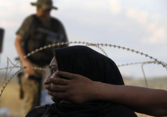 A FYROM  riot policeman stands guard as a Syrian refugee woman sits behind barbed-wire at the Greek-FYROM  border, near the village of Idomeni, August 21, 2015. REUTERS/Yannis Behrakis