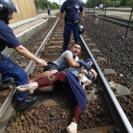 Hungarian policemen stand by the family of migrants as they wanted to run away at the railway station in the town of Bicske, Hungary, September 3, 2015. REUTERS/Laszlo Balogh