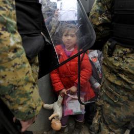 A migrant girl holds her toys as FYROM policemen block migrants at the Greek FYROM borders, near the village of Idomeni, Greece November 20, 2015. REUTERS/Alexandros Avramidis