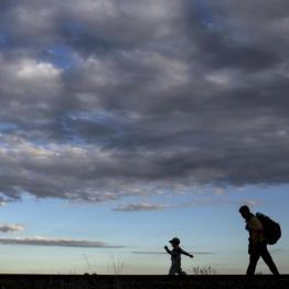 A migrant from Syria walks along rail tracks with his son as they arrive to a collection point in the village of Roszke in Hungary after crossing the border from Serbia, September 6, 2015. REUTERS/Marko Djurica