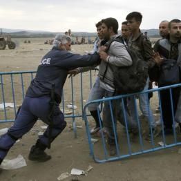 A Greek policeman pushes refugees behind a barrier at Greece's border with FYROM , near the Greek village of Idomeni, September 9, 2015. REUTERS/Yannis Behrakis