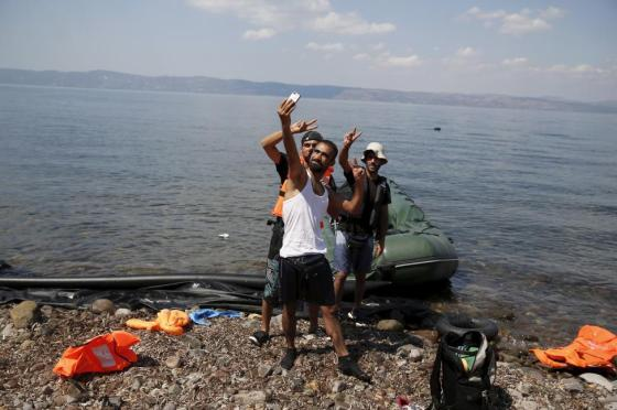 """Syrian refugees from Kobani pose for a """"selfie"""", moments after arriving on a dinghy on the island of Lesbos, Greece August 23, 2015. REUTERS/Alkis Konstantinidis"""