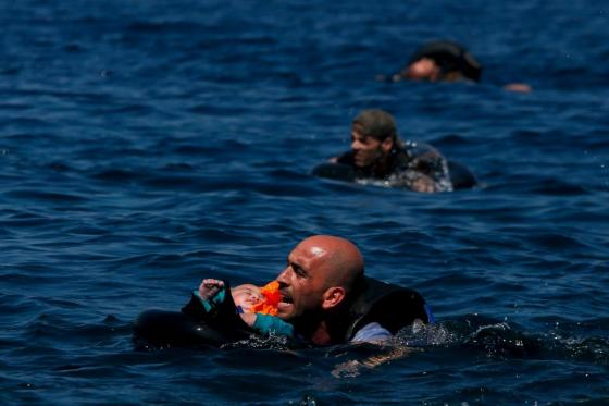 A Syrian refugee holding a baby in a lifetube swims towards the shore after their dinghy deflated some 100m away before reaching the Greek island of Lesbos, September 12, 2015. REUTERS/Alkis Konstantinidis