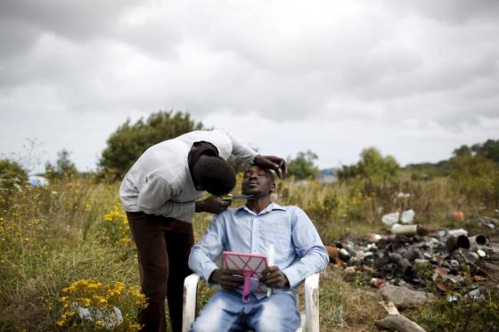 """Sudanese barber Halifa shaves the beard of Ali from Sudan at """"The New Jungle"""" camp in Calais, France, August 6, 2015. REUTERS/Juan Medina"""