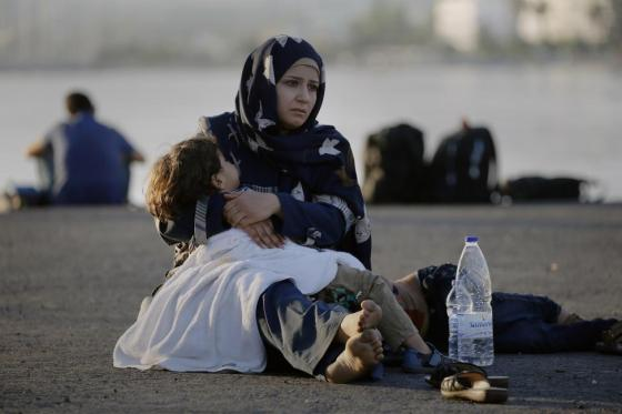 """A Syrian refugee holds her child in her arms as she sits in the port of the Greek island of Kos waiting to be registered and move with her family to the """"Eleftherios Venizelos"""" vessel August 15, 2015. REUTERS/Yannis Behrakis"""