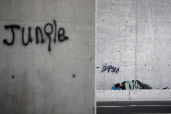 """A migrant sleeps under a busy road bridge, close to the entrance of """"The New Jungle"""" camp in Calais, France, August 9, 2015. REUTERS/ Juan Medina"""