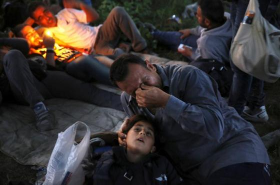 Kurdish Syrian immigrant Sahin Serko cries next to his 7 year-old daughter Ariana minutes after crossing the border into FYROM , near the Greek village of Idomeni in Kilkis prefecture May 14, 2015. REUTERS/Yannis Behrakis
