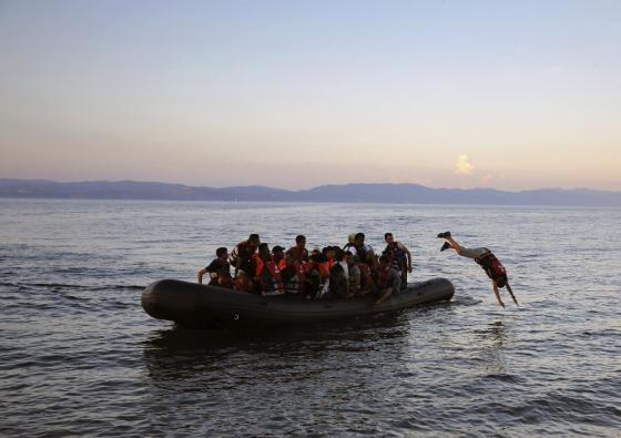 A Syrian refugee dives off an overcrowded dinghy whille approaching a beach on the Greek island of Lesbos, after crossing part of the Aegean Sea from Turkey, September 25, 2015. REUTERS/Yannis Behrakis