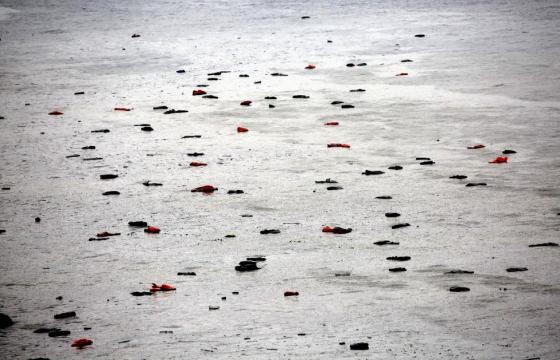 Life vests and tubes left by migrants float by a beach during a rain storm on the Greek island of Lesbos October 21, 2015. REUTERS/Yannis Behrakis