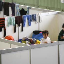 Children watch as they stand on beds in a shelter for migrants inside a hangar of the former Tempelhof airport in Berlin, Germany, December 9, 2015. REUTERS/Fabrizio Bensch