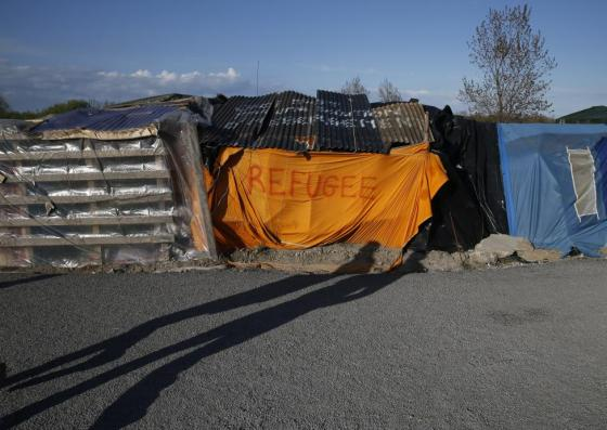 """Shadows from migrants are cast on a makeshift shelter with the written word """"Refugee"""" in Calais, France April 30, 2015. REUTERS/Pascal Rossignol"""