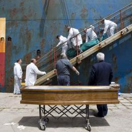 People carry the body of a dead migrant from a merchant ship as they arrive in the Sicilian harbour of Catania, southern Italy, May 5, 2015. REUTERS/Antonio Parrinello