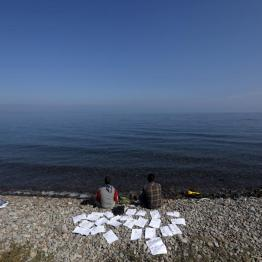 Two Syrian refugee students dry their documents at a beach on the Greek island of Lesbos October 19, 2015. REUTERS/Yannis Behrakis