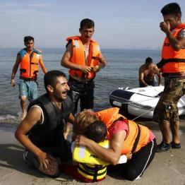An Iranian migrant cries next to his son and wife moments after a small group of exhausted migrants from Iran arrive by paddling an engineless dinghy from the Turkish coast (seen in the background) at a beach on the Greek island of Kos August 15, 2015. REUTERS/Yannis Behrakis