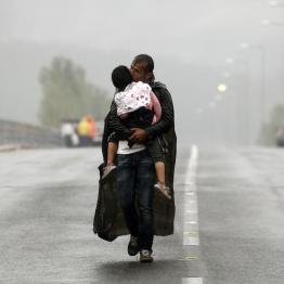 A Syrian refugee kisses his daughter as he walks through a rainstorm towards Greece's border with FYROM , near the Greek village of Idomeni, September 10, 2015. REUTERS/Yannis Behrakis