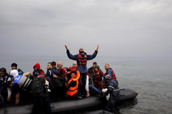 A Syrian refugee gives thanks to God as he arrives in an overcrowded dinghy on the Greek island of Lesbos after crossing part of the Aegean Sea from Turkey September 23, 2015. REUTERS/Yannis Behrakis