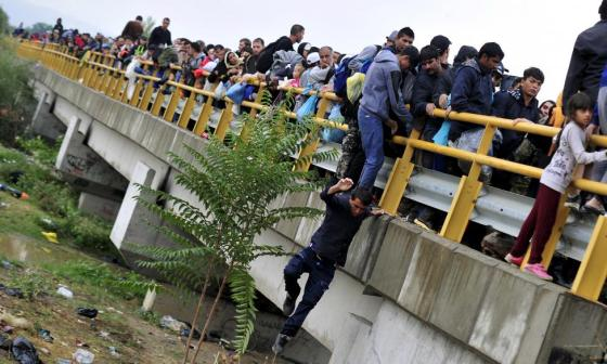 A man jumps down from a bridge, as he and other migrants try to pass police blockades in Gevgelija, FYROM  September 10, 2015. REUTERS/Tomislav Georgiev