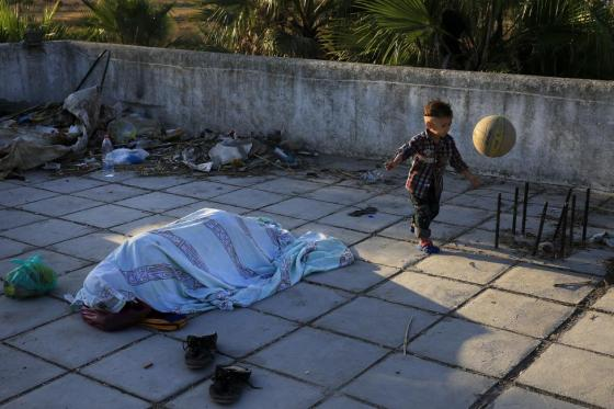 A migrant child from Pakistan plays with a ball as another migrant sleeps at the terrace of a deserted hotel on the Greek island of Kos, August 13, 2015. REUTERS/Alkis Konstantinidis