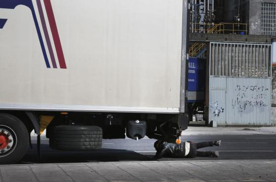 An African immigrant tries to sneak under a truck, which briefly stopped at a traffic light, while trying to enter the ferry terminal in the western Greek town of Patras April 28, 2015. REUTERS/Yannis Behrakis