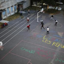 """Migrants play soccer on the basketball court at the Guillaume-Bude secondary school, on which is painted in French """"Solidarity with refugees"""" in Paris, France, August 2, 2015. REUTERS/Stephane Mahe"""