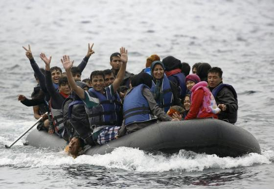 Afghan migrants gesture as they hold onto a compatriot at the side of an overcrowded dinghy, upon arriving at a beach on the Greek island of Lesbos, September 23, 2015. REUTERS/Yannis Behrakis