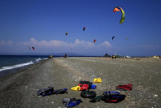 Kitesurfers are seen in the background as abandoned life-jackets used by refugees that arrived this morning are seen on a beach on the Greek island of Kos August 10, 2015. REUTERS/Yannis Behrakis