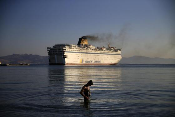 """A migrant washes as the passenger ship """"Eleftherios Venizelos"""" leaves the port on the Greek island of Kos, August 19, 2015. REUTERS/Alkis Konstantinidis"""