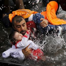 A Syrian refugee holds onto his children as he struggles to walk off a dinghy on the Greek island of Lesbos, September 24, 2015. REUTERS/Yannis Behrakis