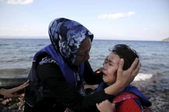 An Afghan mother comforts her crying child moments after a dinghy carrying Afghan migrants arrived on the island of Lesbos, Greece August 23, 2015. REUTERS/Alkis Konstantinidis