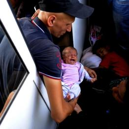A migrant from Aleppo, Syria holds his 30-day-old baby on an overcrowded train as they travel through FYROM August 2, 2015. REUTERS/Ognen Teofilovsk