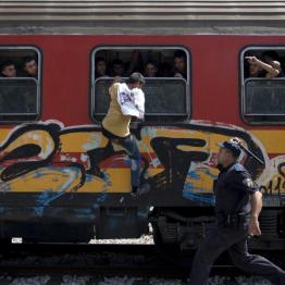 A policeman tries to stop a migrant from boarding a train through a window at Gevgelija train station in FYROM , close to the border with Greece, August 15, 2015. REUTERS/Stoyan Nenov
