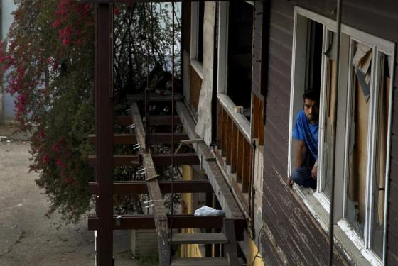 An Afghan immigrant looks out from a wood factory across the street from a ferry terminal in the western Greek town of Patras April 28, 2015. REUTERS/Yannis Behrakis
