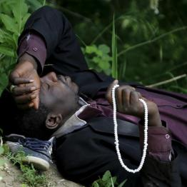 An immigrant from Mali rests at the Greek-FYROM border before an attempt to flee to FYROM May 13, 2015 village of Idomeni in Kilkis prefecture May 13, 2015. REUTERS/Yannis Behrakis