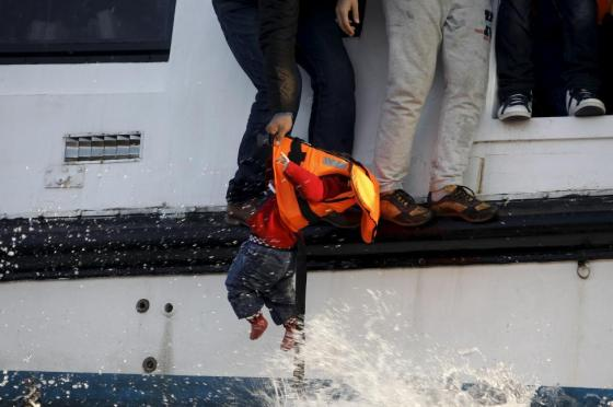 A refugee prepares to hand over a toddler to a volunteer lifeguard, after crossing part of the Aegean sea from Turkey on the Greek island of Lesbos, October 30, 2015. REUTERS/Giorgos Moutafis