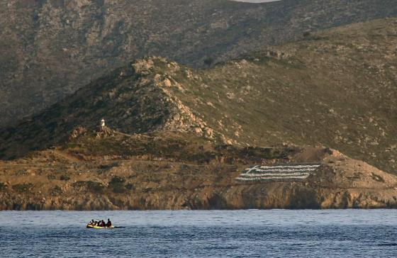 A huge Greek flag is seen painted on the Pserimos coast as unidentified immigrants try to row an engineless dinghy, drifting out of control, off the coast of the Pserimos islet in Greece and the Turkish coast early May 28, 2015.  REUTERS/Yannis Behrakis
