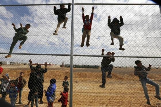 Syrian refugee children climb on a fence to watch a football training workshop in a refugee camp to provide Syrian and Jordanian trainers with football training skills, at Azraq refugee camp near Al Azraq city, Jordan, November 16, 2015. REUTERS/Muhammad Hamed