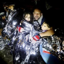 A Syrian refugee tries to keep his children warm after being rescued by Greek fishermen on the Greek island of Lesbos October 19, 2015. REUTERS/Yannis Behrakis