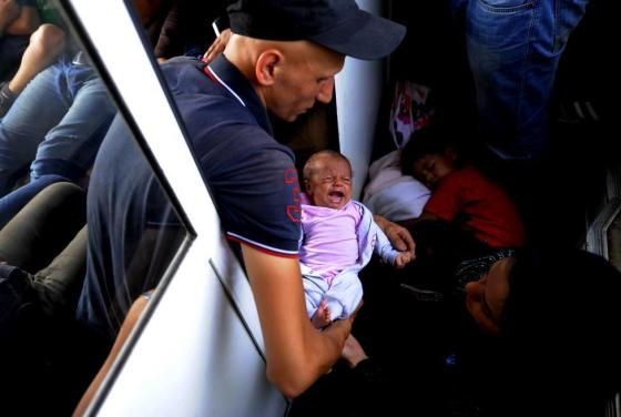 A migrant from Aleppo, Syria holds his 30-day-old baby on an overcrowded train as they travel through Macedonia August 2, 2015. REUTERS/Ognen Teofilovsk