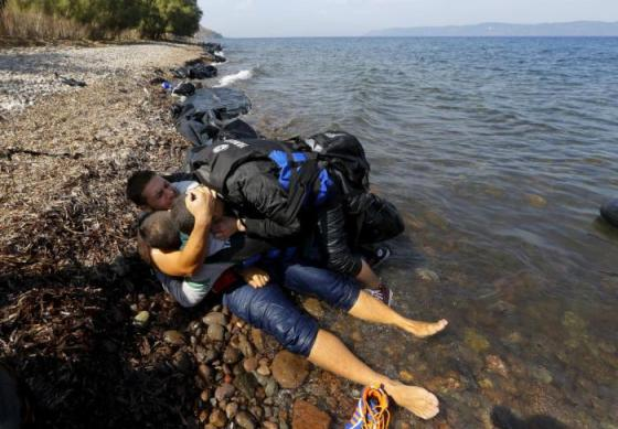 Young Syrian refugees react after disembarking from an overcrowded dinghy upon arriving at a beach on the Greek island of Lesbos, September 26, 2015. REUTERS/Yannis Behrakis