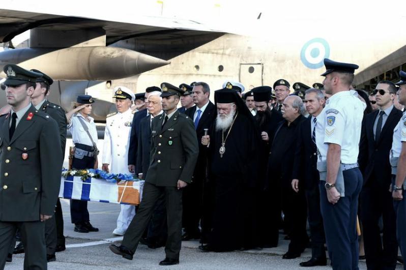 Η φωτογραφία τραβήχτηκε τον Οκτώβριο στην αεροπορική βάση Δεκέλειας στο Τατόι, στην επίσημη υποδοχή από την Ελληνική Πολιτεία των λειψάνων των Ελλήνων πεσόντων στην Κύπρο, στην οποία παρέστη και ο Ηλίας Κασιδιάρης