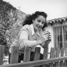 Elizabeth Taylor eating a hamburger on a fence. Circa 1949