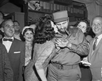 Gladys Feijoo, 19-year-old Miss La Prensa of 1959, kisses Fidel Castro as he signs his autograph for her collection on April 22, 1959.