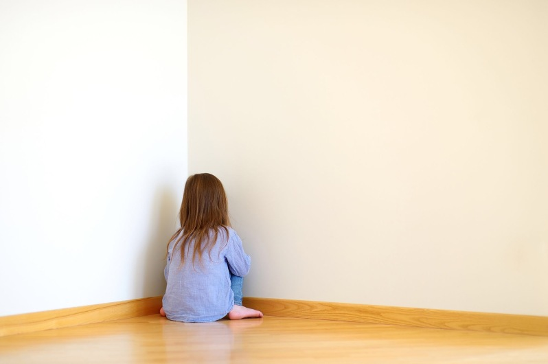 Sad little girl sitting in a corner