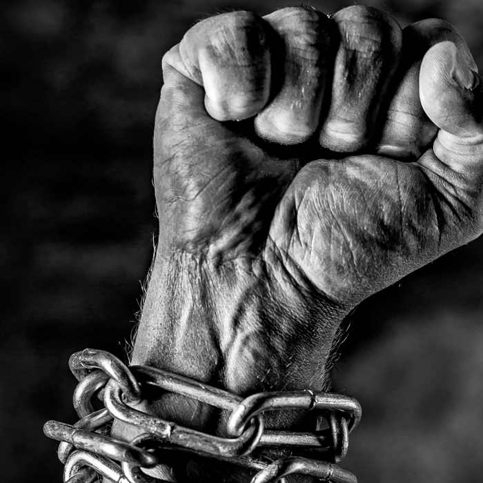 Arm in chains and the hand is closed as a fist, struggle free from oppression and tyranny , Fist in chains john holloway crack capitalism